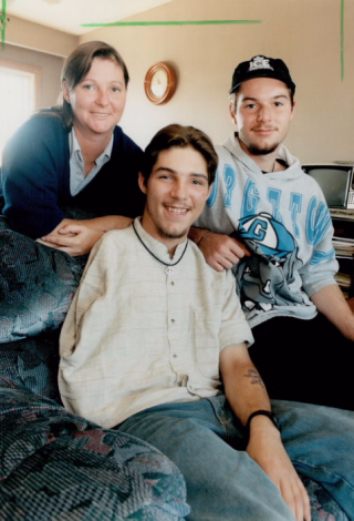 Photograph of Scott Conner as a young man, seated, smiling at the camera, with his mother Sandi standing on one side of him and brother Adam on the other