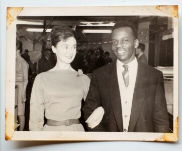 black and white photo of James Ssali and and unknown woman dressed smartly and standing arm-in-arm before the camera