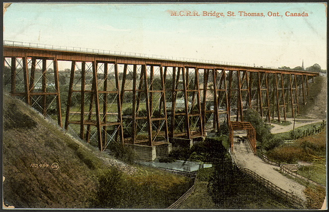 A coloured postcard of a steel trestle bridge with a roadway and trees under it.
