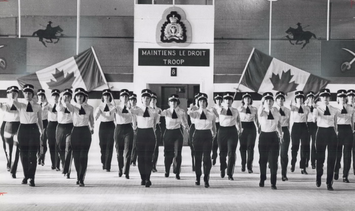 Lines of female recruits of Royal Canadian Mounted Police marching with Canadian flags