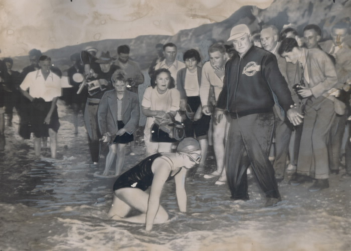 Swimmer Marilyn Bell crawls onshore in front of a crowd of photographers, while her swim coach holds them back.